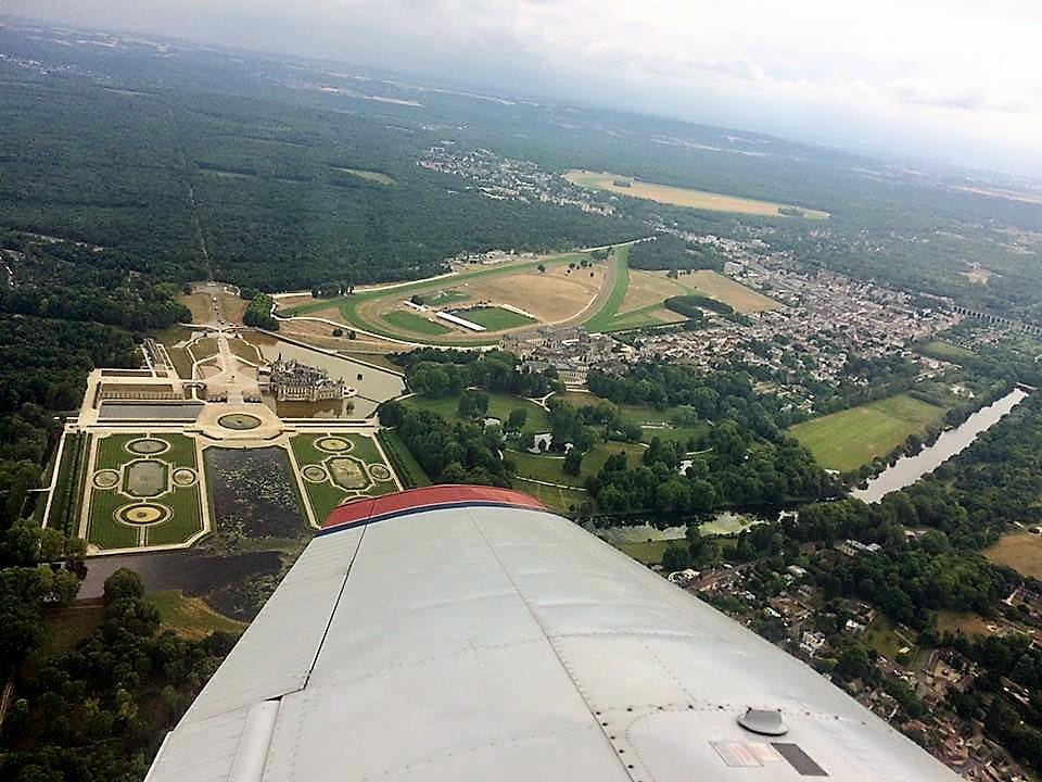 Voler permet de redécouvrir notre patrimoine autrement. Ici, le survol du château de Chantilly en Piper PA-28.